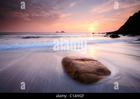 Porth Nanven, a stunning location in Cornwall, at sunset with a low tide breaking around a rock. - Stock Photo