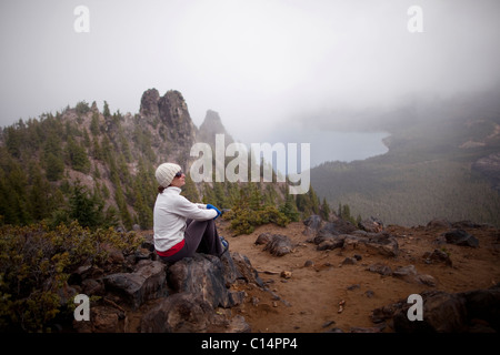 A young woman rests after hiking around the rim of Newberry Volcano east of the Cascade range near Bend, Oregon - Stock Photo