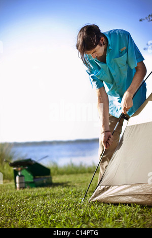 Young man assembles a tent on the banks of Shelby Lakes in Gulf Shores Alabama. - Stock Photo