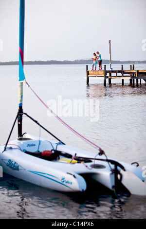 Two girls fish off a pier on the Santa Rosa Sound, Pensacola Beach, Florida. - Stock Photo