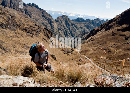 A young man reflects at the summit of Dead Woman's Pass on the Inca Trail. - Stock Photo