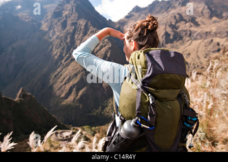 A young woman looks into the distance over some ancient Incan ruins along the Inca Trail. - Stock Photo