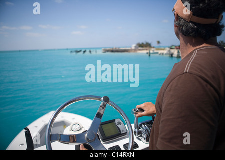 A fisherman steers his boat and hits the throttle from the fly bridge as he gazes out at the blue-green tropical - Stock Photo