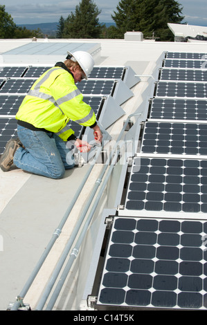 Green energy technician adjusts photovoltaic panels on a roof - Stock Photo