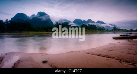 Small stone, river and mountains covered in mist.  Vang Vieng, Laos, Asia. - Stock Photo
