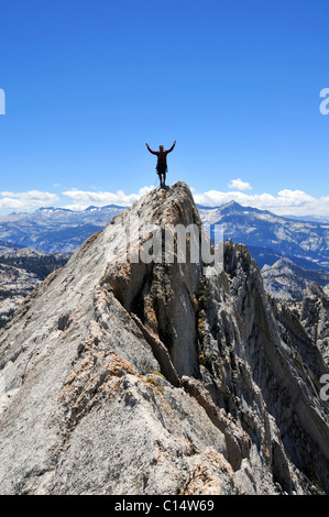 A rock climber stands with arms outstretched on Matthes Crest in Yosemite National Park, California. - Stock Photo