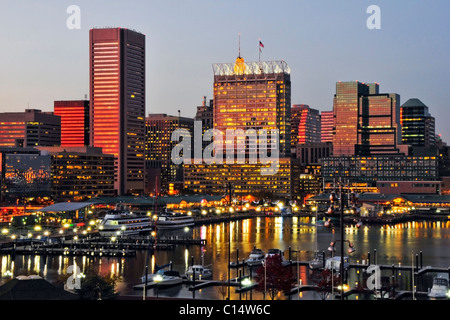 The sunset reflects off the windows of the Baltimore city skyline at dusk, Maryland. - Stock Photo