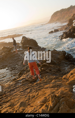 Couple exploring tide pools along Pacific Ocean near Moonstone Beach in Cambra, California. California Central Coast. - Stock Photo