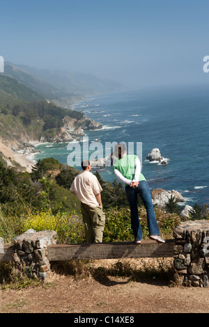couple looking at cliffs pacific ocean view from highway 1 in big sur california
