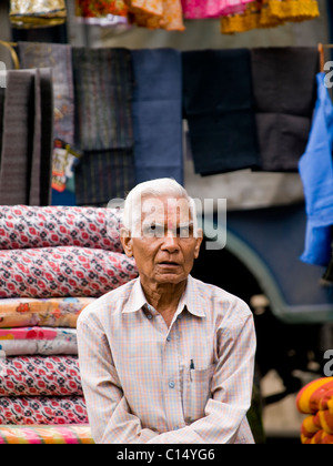 Man selling all kinds of wares on a market - Stock Photo