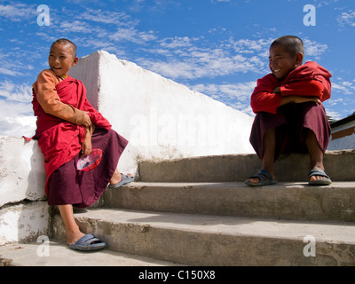 Young smiling monks sitting in front of a temple. - Stock Photo