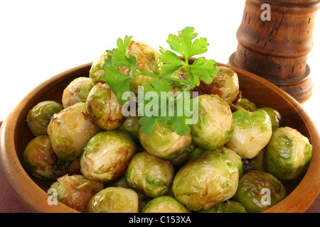 roasted brussels sprouts in a wooden bowl on a brown napkin - Stock Photo