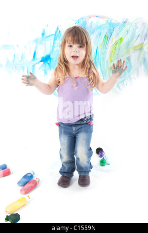 child painting with paint on herself looking at camera - Stock Photo