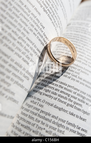 Gold ring on a book casting a heart shapped shadow Stock Photo