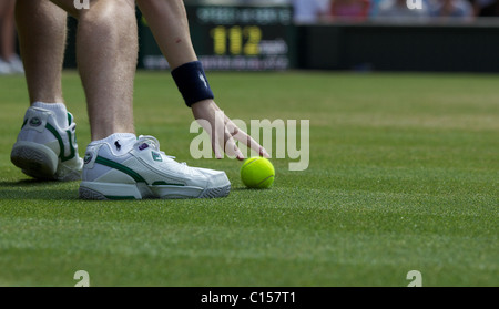 A ball boy collects the ball during competition at the All England Lawn Tennis Championships at Wimbledon, London - Stock Photo