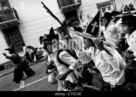 Indians, wearing white shirts, dance and shout furiously during the Inti Raymi (San Juan) festivities in Cotacachi, - Stock Photo