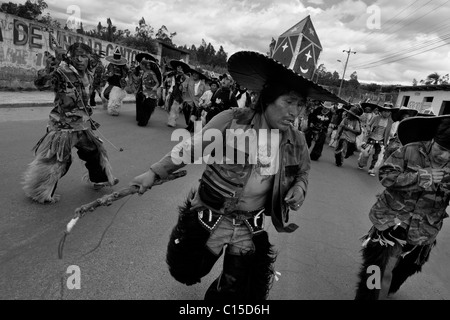 Indians, wearing military camouflage, dance furiously during the Inti Raymi (San Juan) festivities in Cotacachi, - Stock Photo