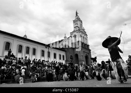 Indians, wearing goatskin chaps, dance furiously during the Inti Raymi (San Juan) festivities in front of the church - Stock Photo