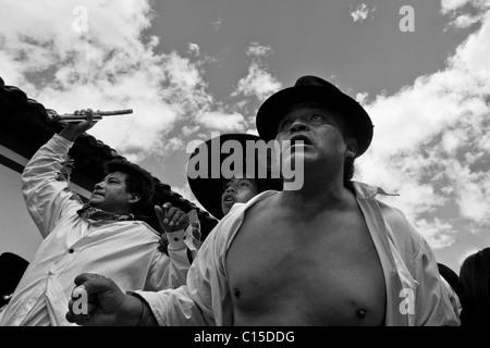 Indians, wearing white shirts, dance and shout during the Inti Raymi (San Juan) festivities in Cotacachi, Ecuador. - Stock Photo
