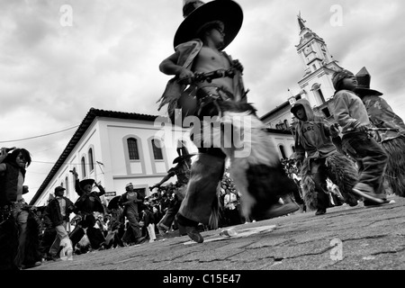 Indians, wearing goatskin chaps, dance furiously during the Inti Raymi festivities in front of the church in Cotacachi, - Stock Photo