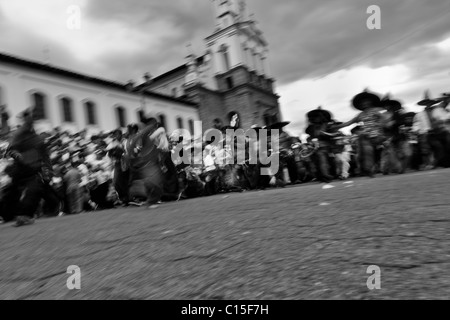 Indians dance furiously during the Inti Raymi (San Juan) festivities in front of the church in Cotacachi, Ecuador. - Stock Photo