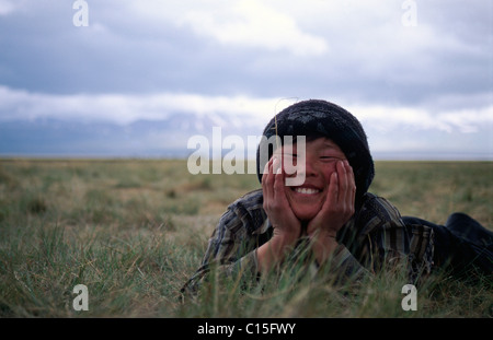 Nomad boy lying in the grass, Song-Kul, Kyrgyzstan, Central Asia - Stock Photo