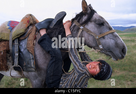 Nomad boy playing with his horse, Song-Kul, Kyrgyzstan, Central Asia - Stock Photo