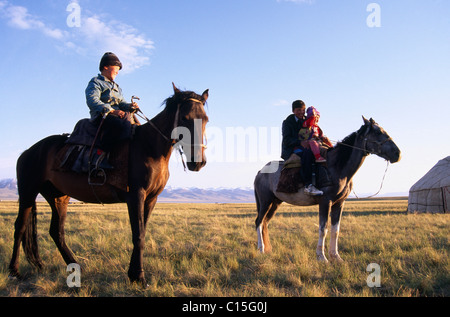 Nomad children on their horses, riding horseback, Song-Kul, Kyrgyzstan, Central Asia - Stock Photo