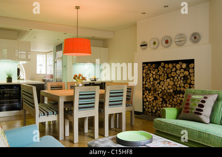 Large orange lampshade above dining table in open plan kitchen room with firewood