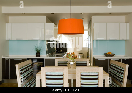 Large orange lampshade above dining table in open plan kitchen with striped chairs - Stock Photo