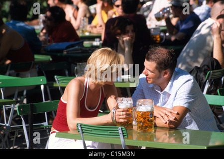 Couple drinking beer in the beer garden near Chinesischer Turm, Chinese Tower in the Englischer Garten, English - Stock Photo