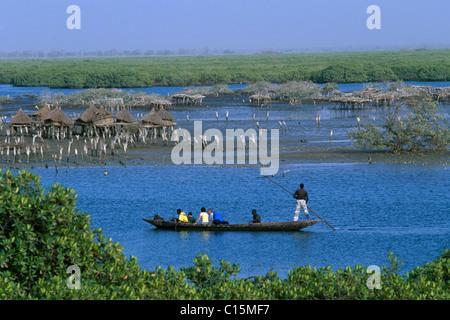 Canoe passing storage houses at Joal-Fadiouth, Senegal, Africa - Stock Photo