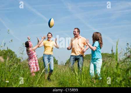 Family throwing football on a meadow - Stock Photo
