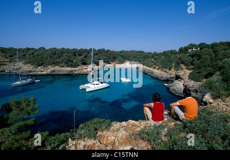 Couple sitting on rocks in the Cala Sa Nau Bay, Balearic Islands, Europe - Stock Photo