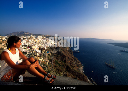 Woman sitting on the edge of a crater looking down onto Thira, Santorini, Cyclades, Greece, Europe - Stock Photo