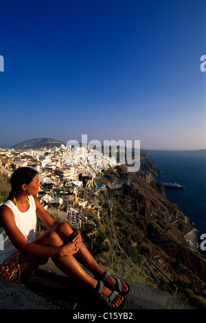 Woman sitting on the edge of a crater, looking down onto Thira, Santorini, Cyclades, Greece, Europe - Stock Photo