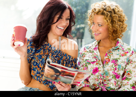 Two girls relaxing reading a magazine - Stock Photo