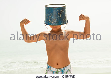 Boy with bucket on head, flexing muscles - Stock Photo