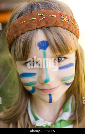 Girl dressed in Native American costume with face painted - Stock Photo