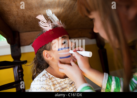 Girl putting Native American face paint on another girl - Stock Photo