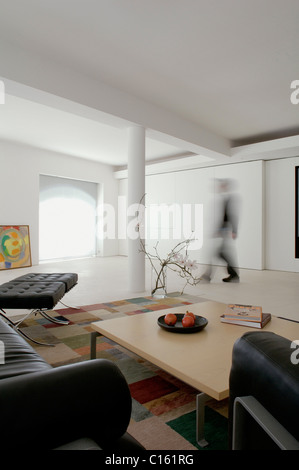 Black Barcelona chairs in seating area with coffee table and checked carpet within open plan white warehouse conversion