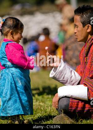 Young girl in a traditional Kira gets candy from her father - Stock Photo