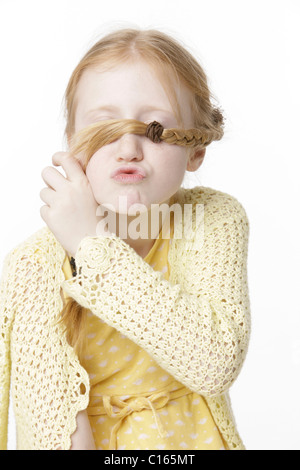 Girl, 8, making a face and holding a braid in front of her eyes - Stock Photo