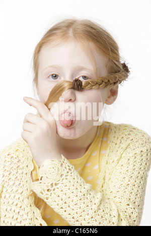 Girl, 8 years old, making a face and holding a braid across her face - Stock Photo