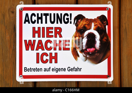 Sign, danger! I guard here enter, at your own risk, picture of a Boxer dog - Stock Photo