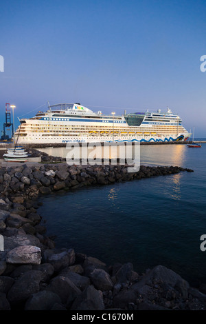 The luxury cruise liner AIDAblu at dusk leaving the harbour of Puerto del Rosario on the Canary Island of Fuerteventura - Stock Photo