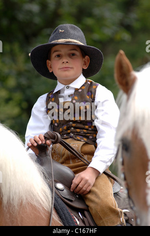 Young boy horseman riding a Haflinger horse during a traditional procession in the village of Santa Cristina in - Stock Photo