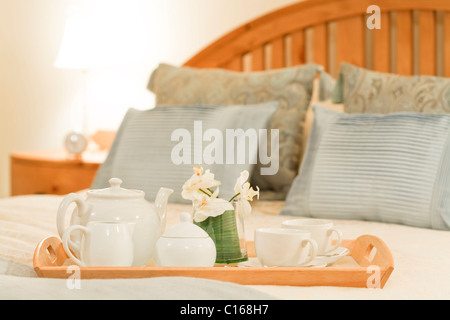 Breakfast tray on a bed in a traditional style bedroom - Stock Photo