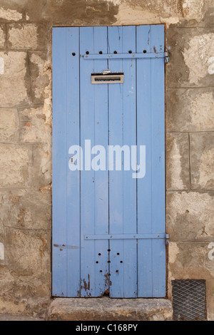 Traditional wooden door in faded blue paint, set in an ancient stone wall - Stock Photo