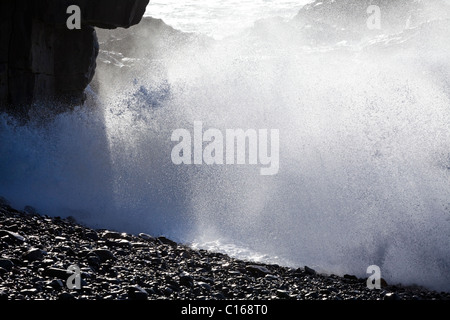 Heavy Atlantic seas with large waves crashing onto rocks at Ajuy on the Canary Island of Fuerteventura - Stock Photo